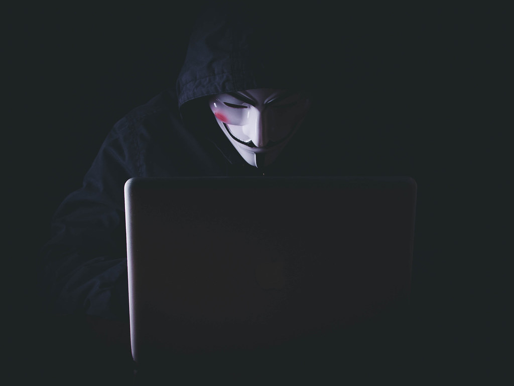 Anonymous man in mask and hoodie sitting near laptop