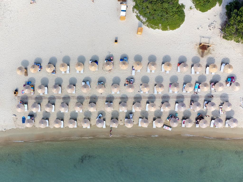 Ansicht von oben: vier Reihen Sonnenschirme am Sandstrand mit türkisem Wasser auf Tsoungria
