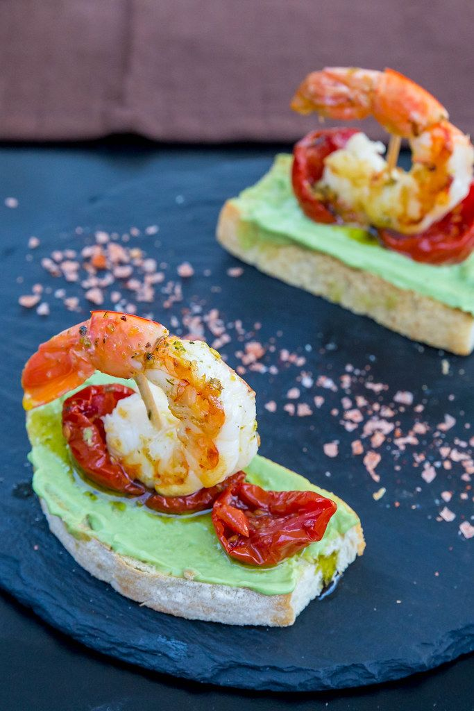 Appetizer at Q11, Pollença: two slices of toasted bread with avocado, dried tomatoes, king prawns
