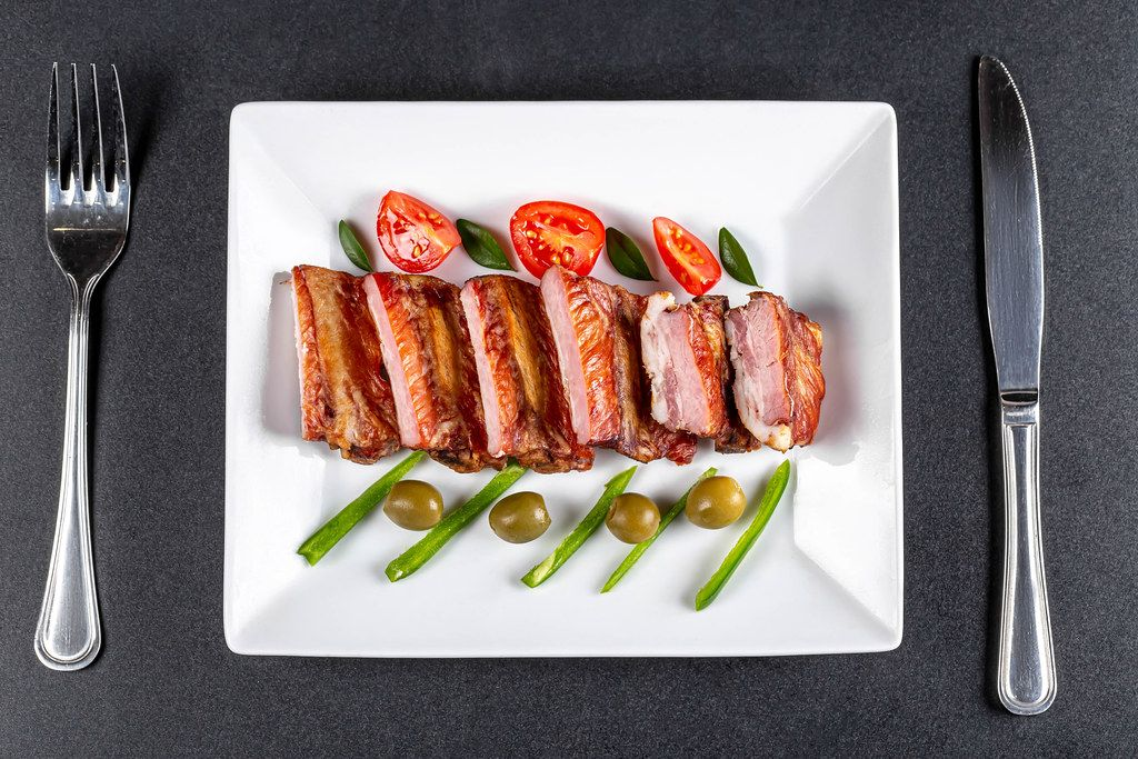 Appetizing smoked ribs with tomatoes, jalapenos and olives, top view