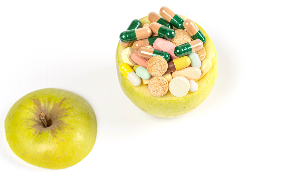 Apple filled with multi-colored medical pills and capsules on a white background