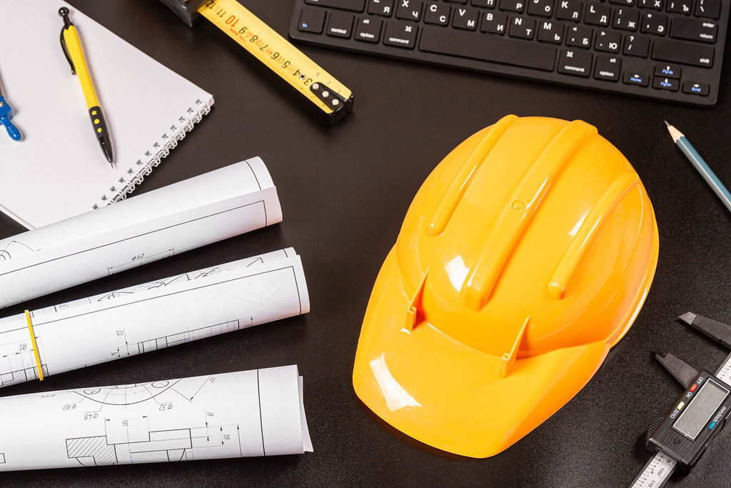 Architectural or engineering profession background with hard hat and blueprints