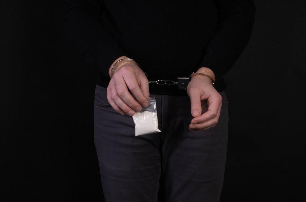 Arrested dealer holds a little bag of drugs