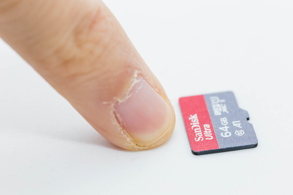 As small as a fingernail: close-up of Micro SD card SanDisk Ultra 64 GB on white background