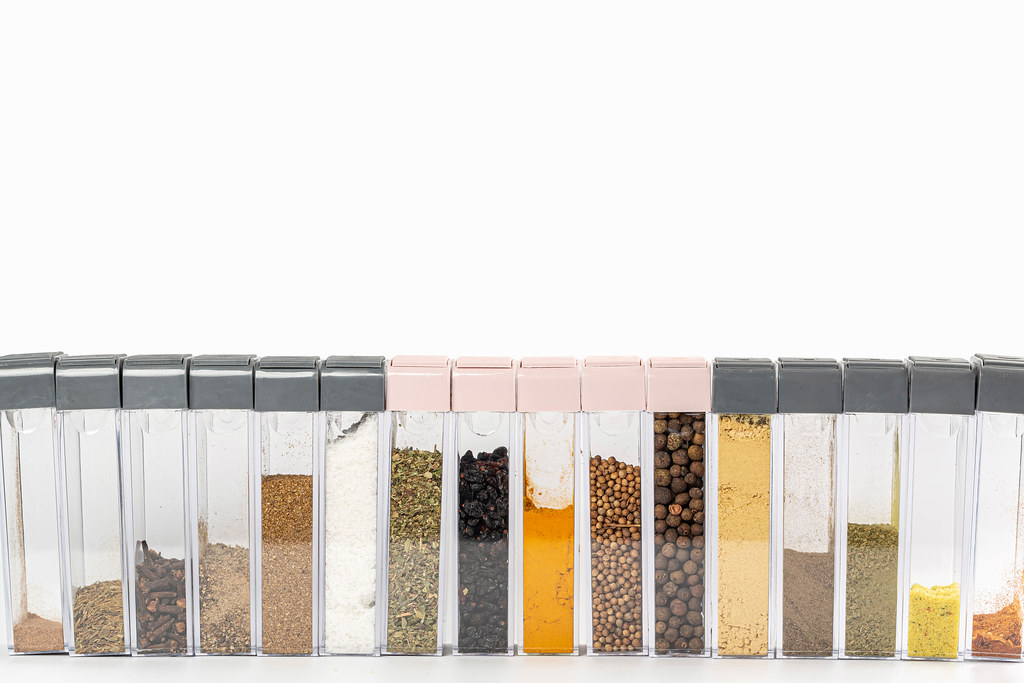 Assorted multi colored spices in boxes on white