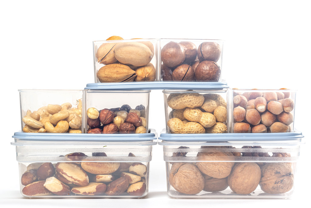 Assortment of different nuts in plastic containers on a white