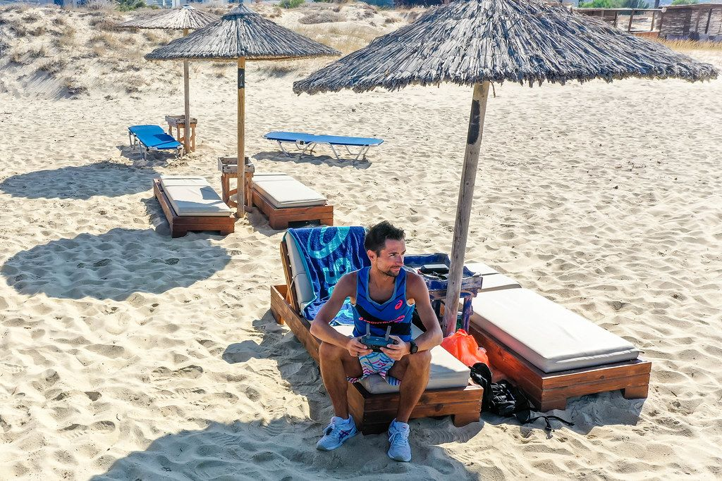 At the beach with the drone controller: taking aerial photos from the sunbed on holiday in Naxos, Greece