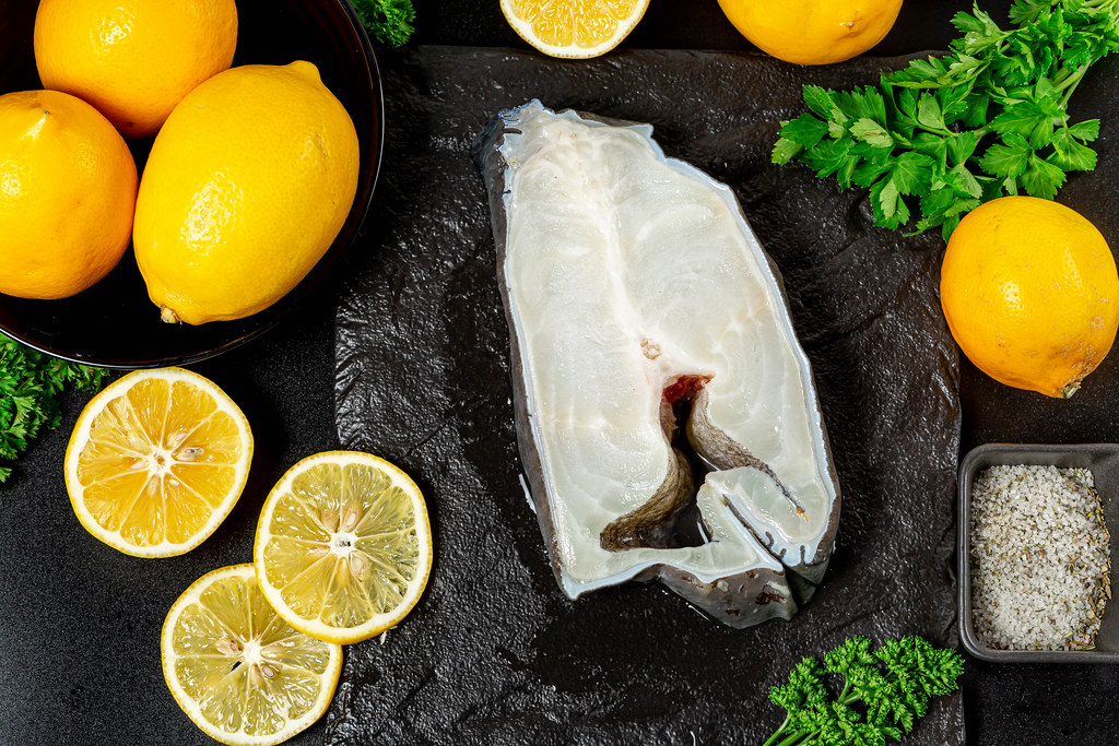 Atlantic wolffish steak on dark background with lemons slices