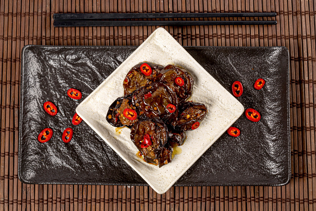 Aubergines with hot pepper on dark background, top view