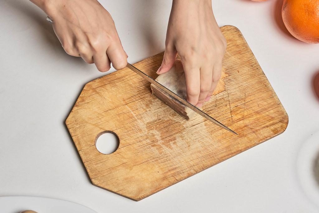 Aufnahme von oben: Hände mit Messer schneiden zubereitetes Rinderzungefleisch auf einem Holzbrett