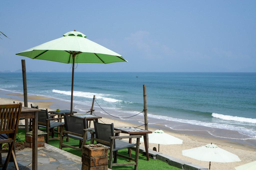 Außenbereich mit Stühlen, Tischen und Sonnenschirm im Sound of Silence Cafe mit Blick auf das Meer am An Bang Strand in Hoi An, Vietnam