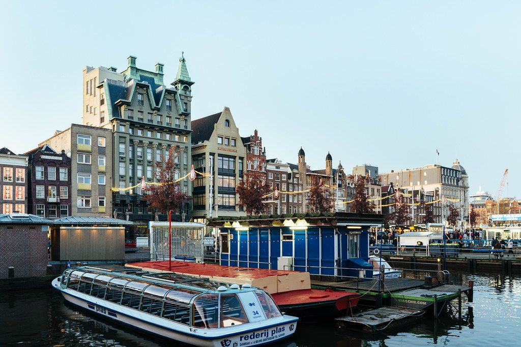 Authentic old buildings in downtown Amsterdam with pier and boats in the foreground