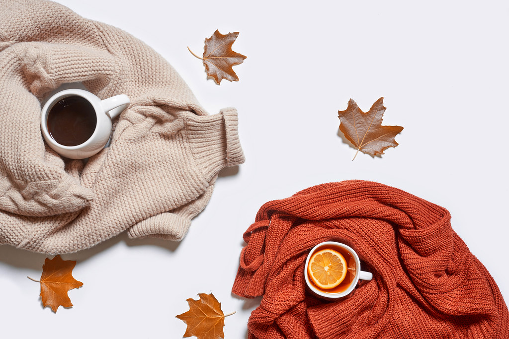 Autumn background with fall leaves, cup of tea and coffee on white table