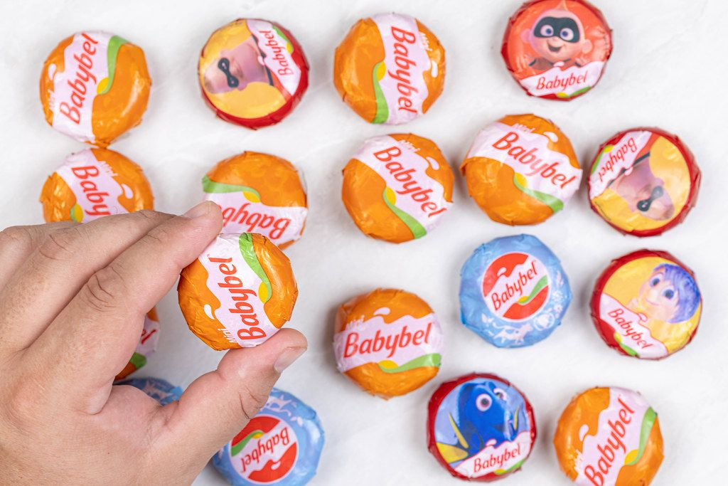 Babybel small cheese packed in small packages in the hand