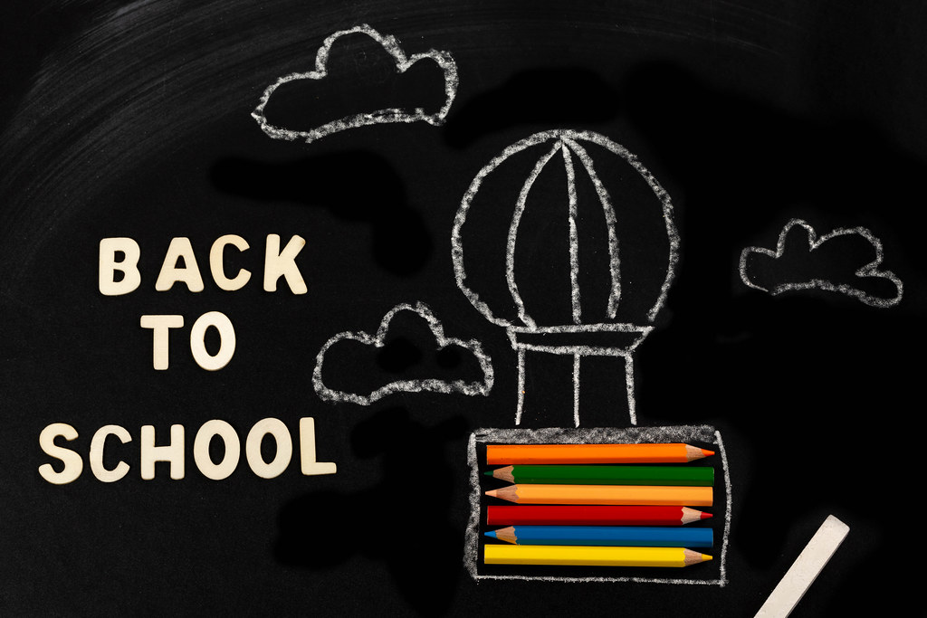 Back to school background with air balloon and pencils