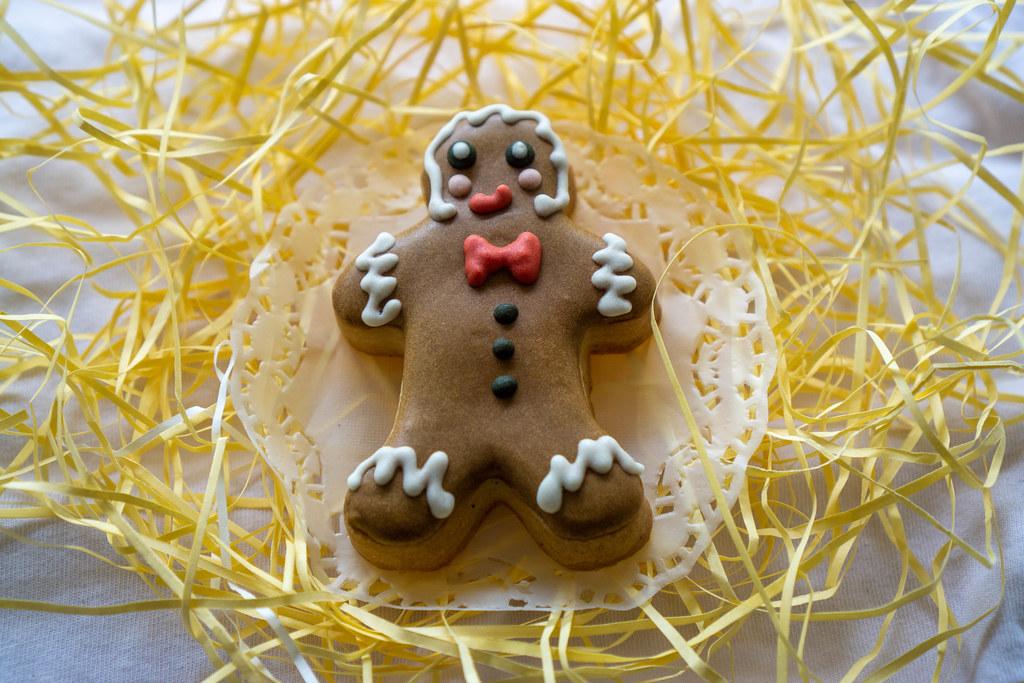Backen zu Weihnachten Lebkuchenmann mit Zuckerglasur dekoriert auf weißem Papier