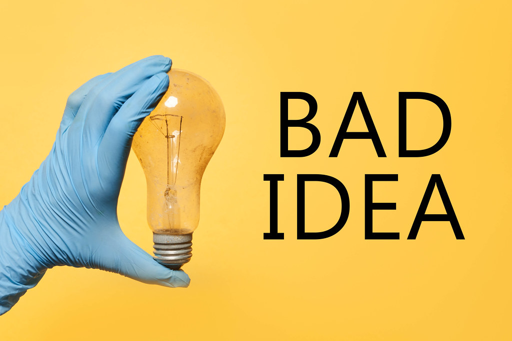 Bad idea - hand in medical gloves holding an old dirty bulb over yellow background