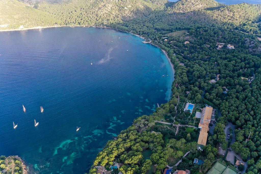 Badia de Pollença, Cala Pi de la Posada: drone shot of pine-covered bay and Hotel Formentor, Majorca