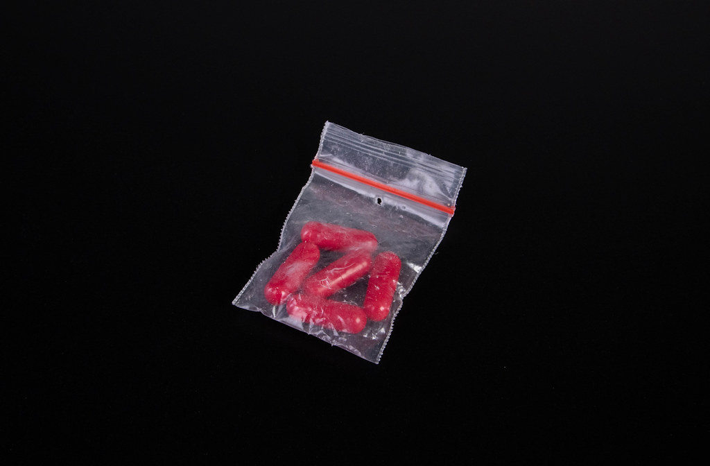 Bag with red pills on black background
