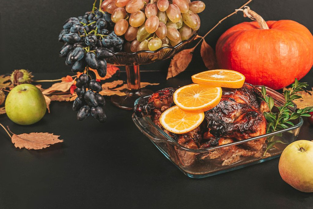 Baked chicken on a dark background with pumpkin, fruits and autumn leaves