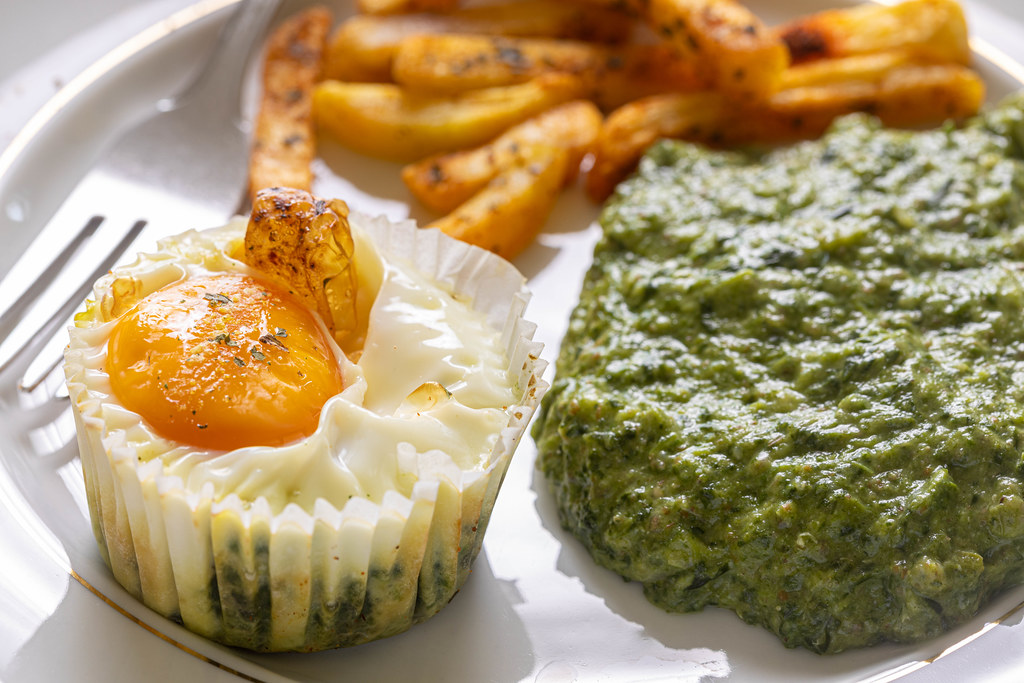 Baked Egg with Spinach and french fries on the plate