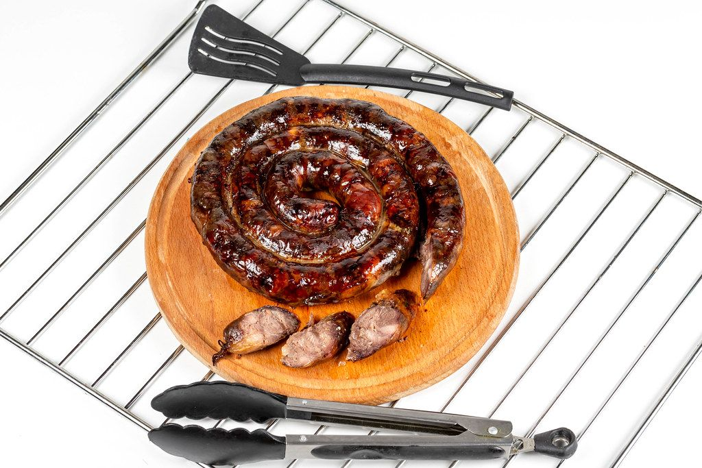 Baked homemade sausage on kitchen board with slices