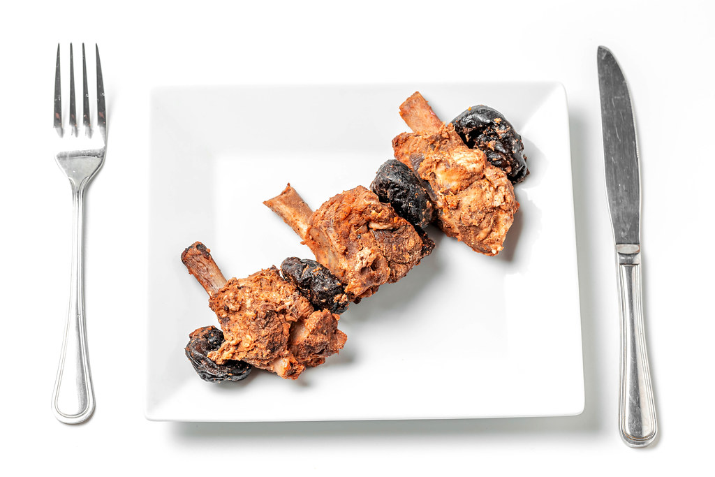 Baked pork ribs with prunes on a white plate with a knife and fork