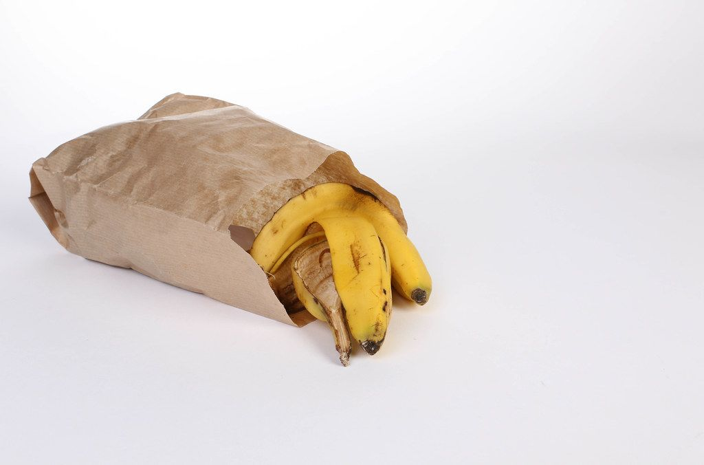 Banana peels in a paper bag on white background