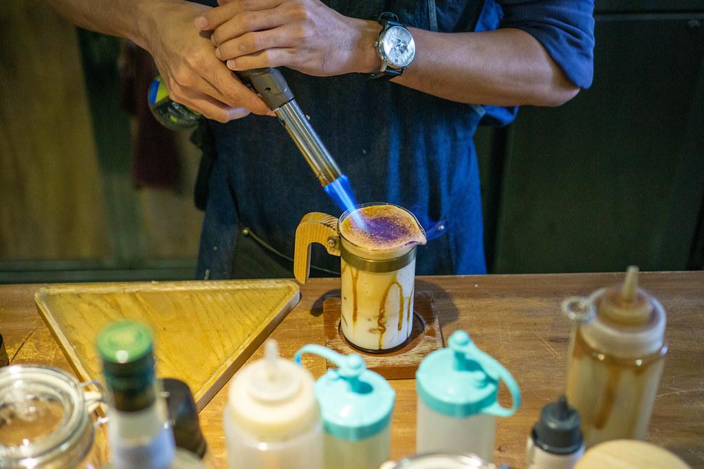 Barista preparing a Dalgona Coffee and using a Gas Burner to caramelize Sugar in a Coffee Shop