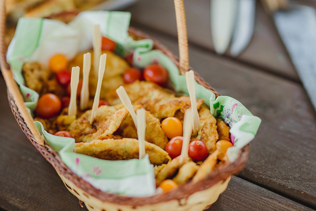 Basket With Pancakes And Tomatoes On Wooden Table
