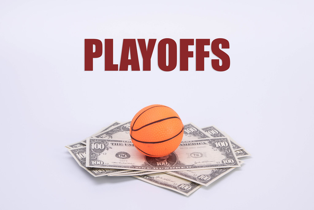 Basketball ball on US dollar banknotes with Playoffs text