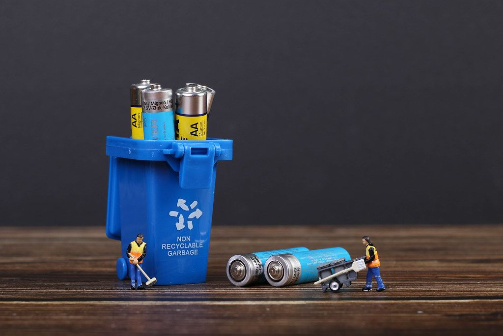 Batteries in blue recycle bin with tiny cleaning workers