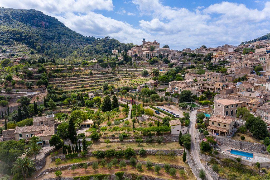 Bäume auf terrassierten Hügeln, Häuser mit Pools, das ehemalige Kloster von Valldemossa. Luftbild
