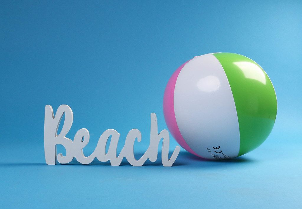 Beach ball with beach text on blue background
