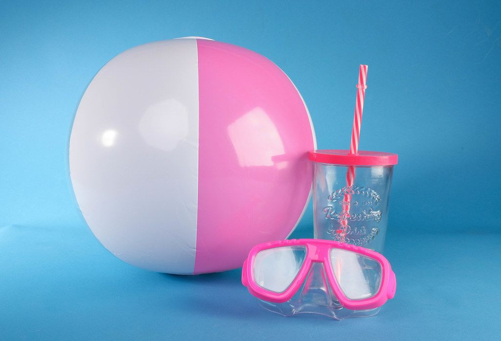 Beach ball with diving mask and drinking glass on blue background