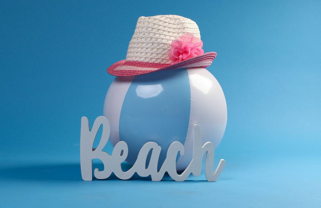 Beach ball with sun hat and beach text on blue background