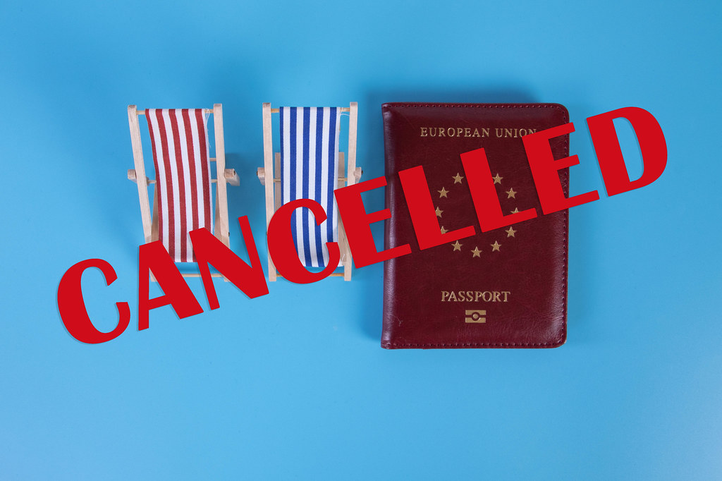 Beach chairs with passport and Cancelled text on blu background