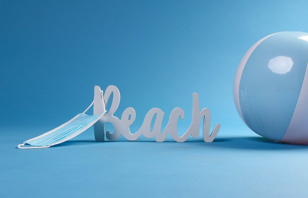 Beach text with beach ball and medical face mask on blue background