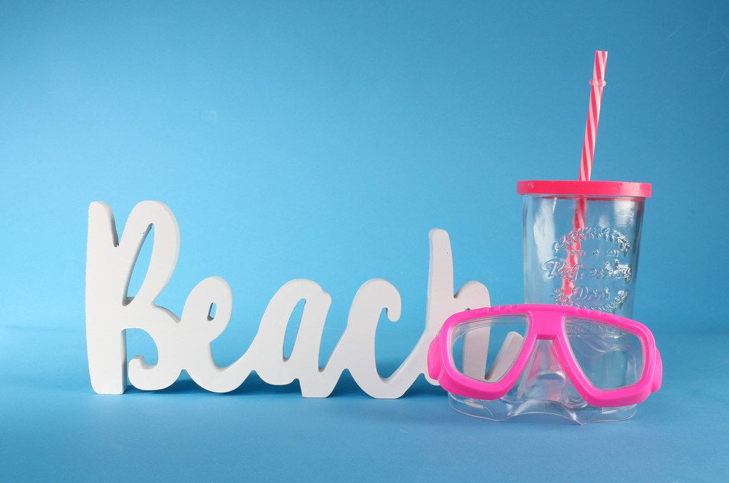Beach text with diving mask and drinking glass on blue background