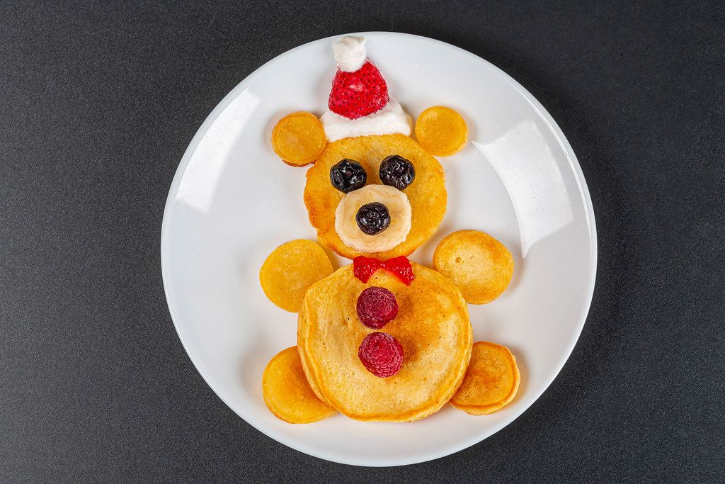 Bear pancakes with berries for kids breakfast on black background, top view