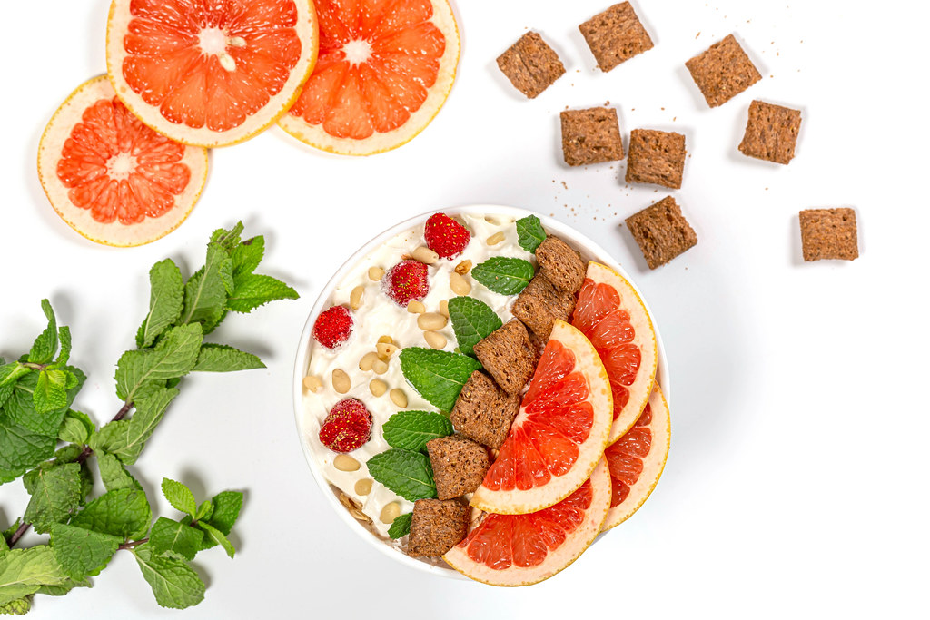 Beautiful breakfast background with oatmeal grapefruit, mint and chocolate pads, top view