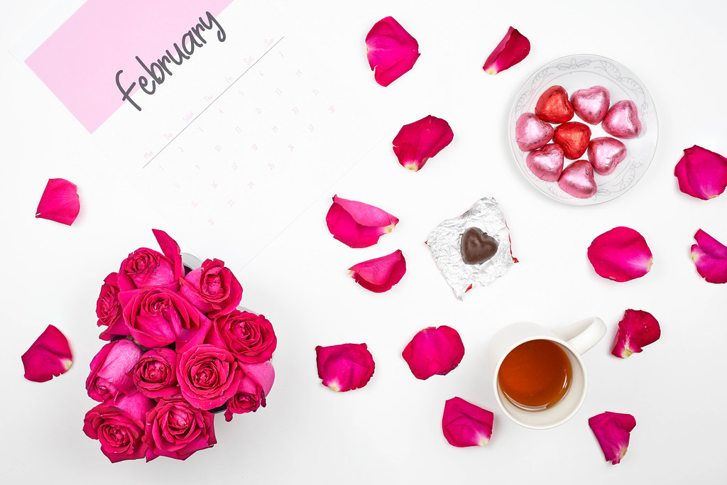 Beautiful rose flower petals, heart shape sweet chocolates and February calendar