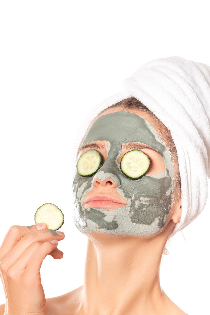 Beautiful young woman with clay mask on her face holding slices of fresh cucumber, skin care and treatment and cosmetology concept