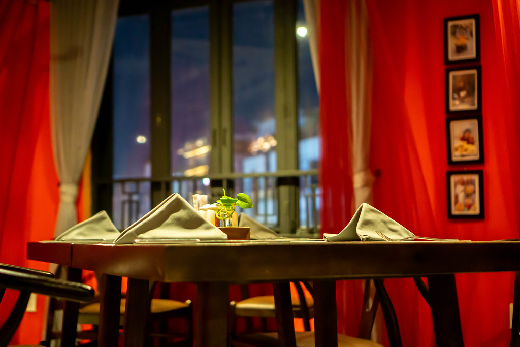 Beautifully Set Table with Cutlery, Napkin and a Small Table Plant at a Middle Eastern Restaurant with White and Red Curtains in the Background