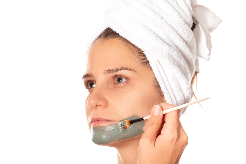 Beauty procedures skin care concept, woman no makeup applying facial gray clay mask to her face