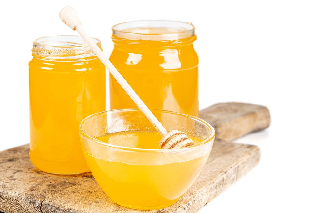 Bee honey in glass jars and a bowl with a wooden honey dipper