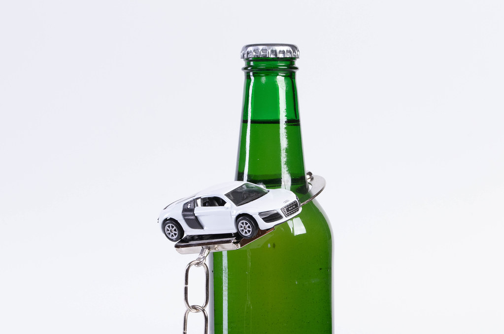 Beer bottle with handcuffs and miniature car on white background