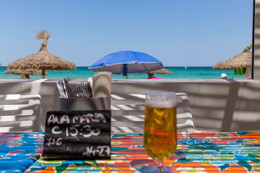 Beer by the sea. Draught beer, reservation card and cutlery with beach umbrellas in the background