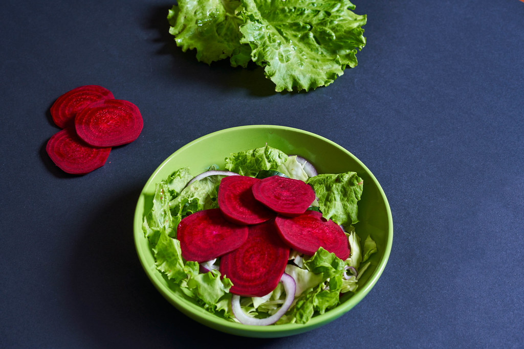 Beetroot salad with lettuce leaves on dark background
