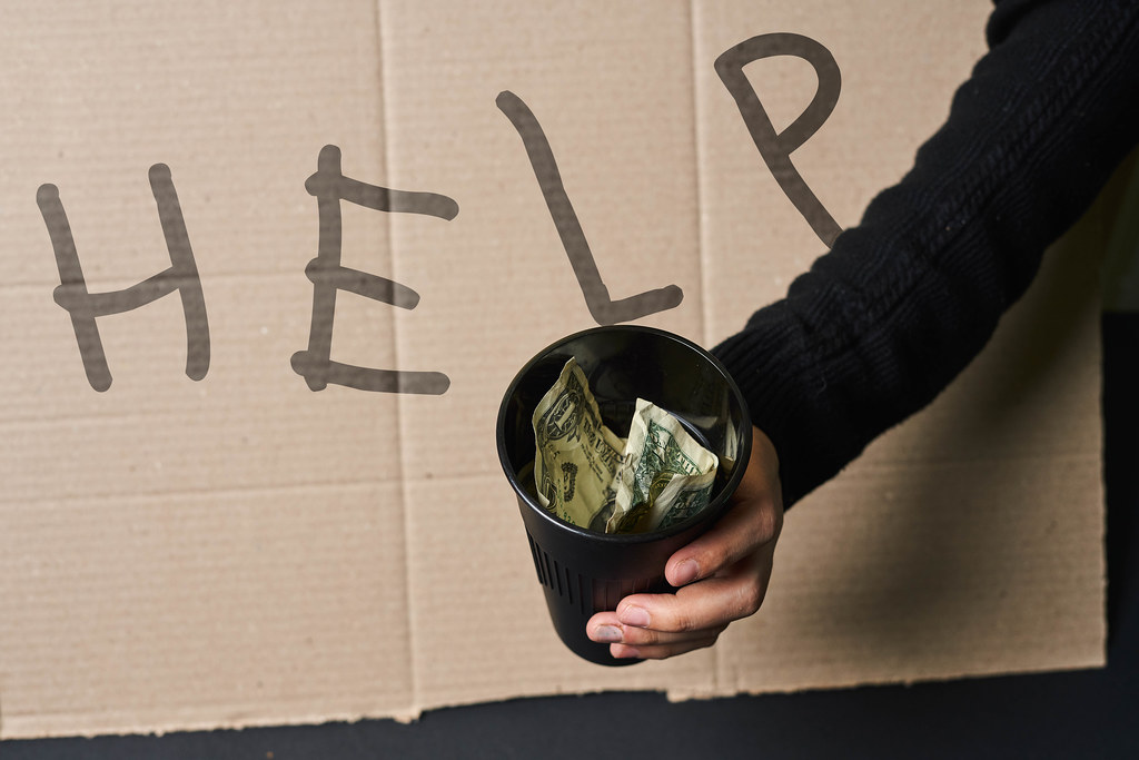 Beggar showing Help sign on cardboard